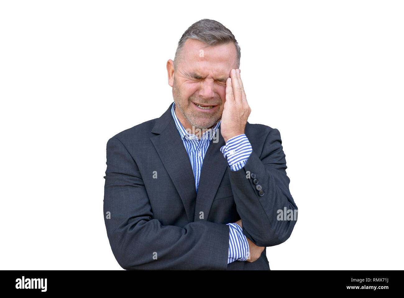Stressed businessman, or suffering from a headache, standing with his hand to his temple grimacing against white background - Stock Image