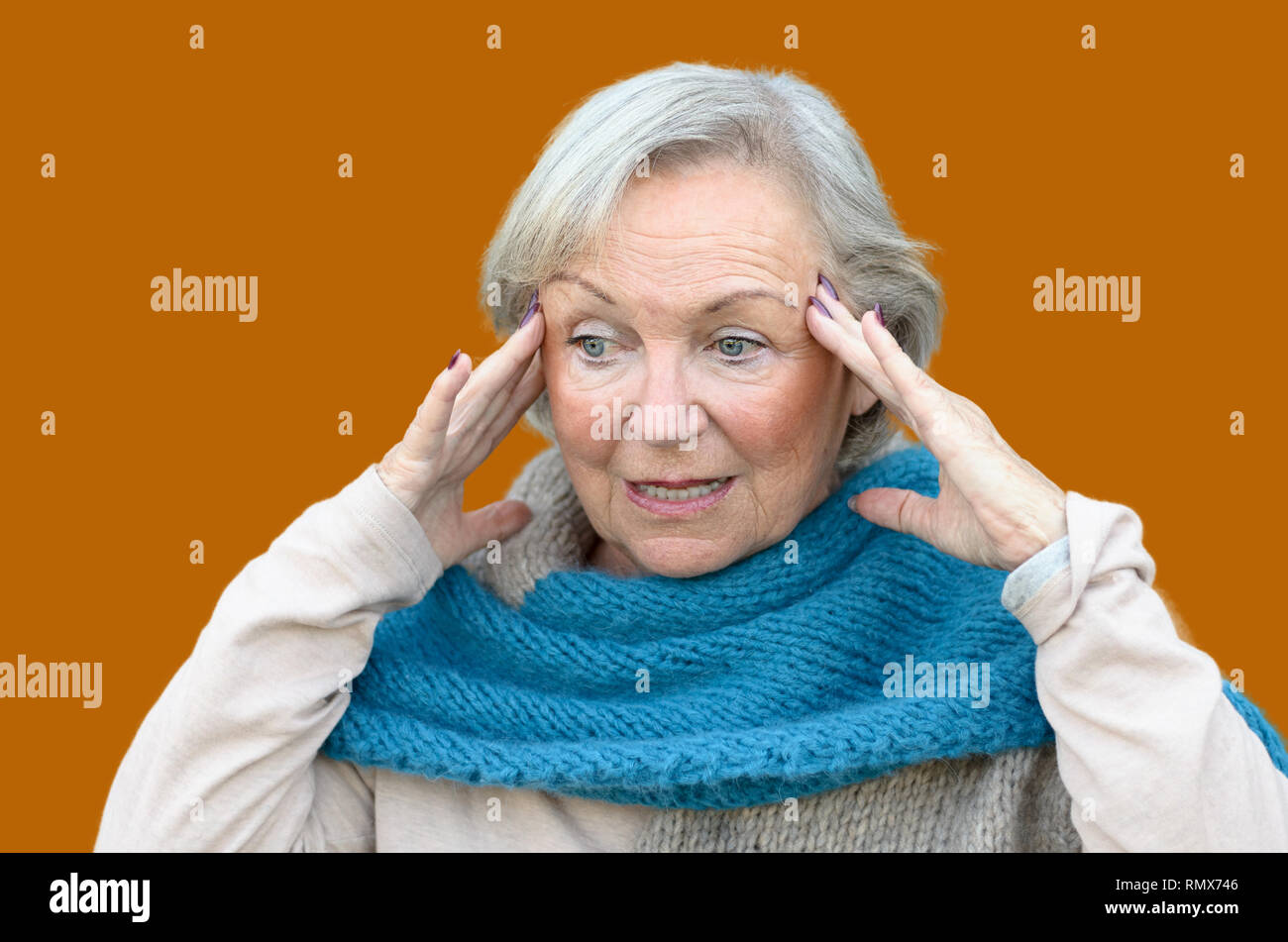 Confused and bewildered senior lady holding her hands to her temples as she looks aside, conceptual of the onset of dementia or Alzheimers disease - Stock Image