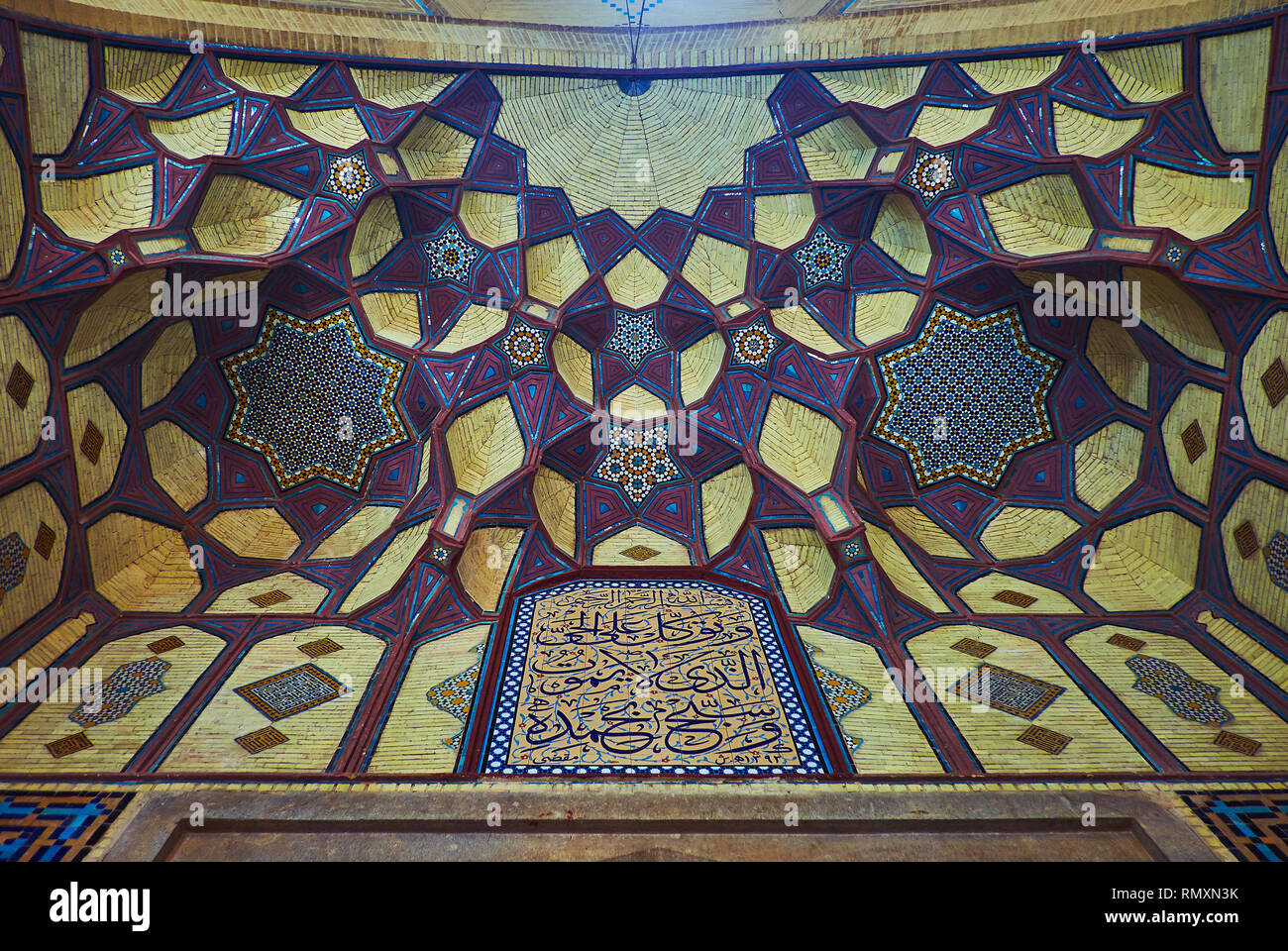 ISFAHAN, IRAN - OCTOBER 21, 2017: The arch of the portal (iwan) of Honar Bazaar is decorated with brick muqarnas and covered with bright stellar patte - Stock Image