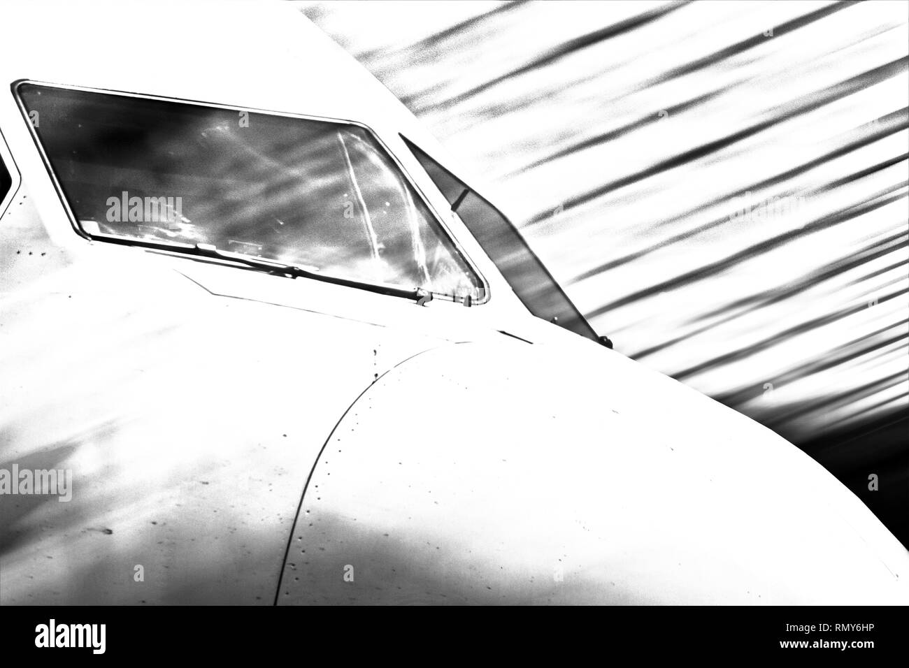 Black and white image of airplane cockpit seen from exterior with motion blur strokes pattern in the background. - Stock Image