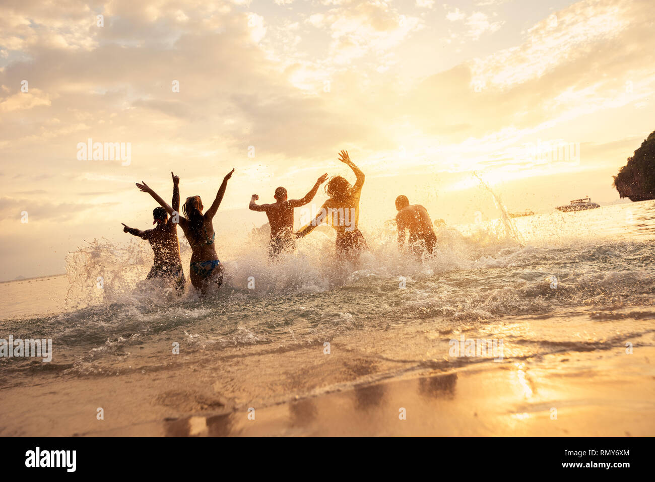 Happy friends runs or having fun at idyllic sunset sea Stock Photo
