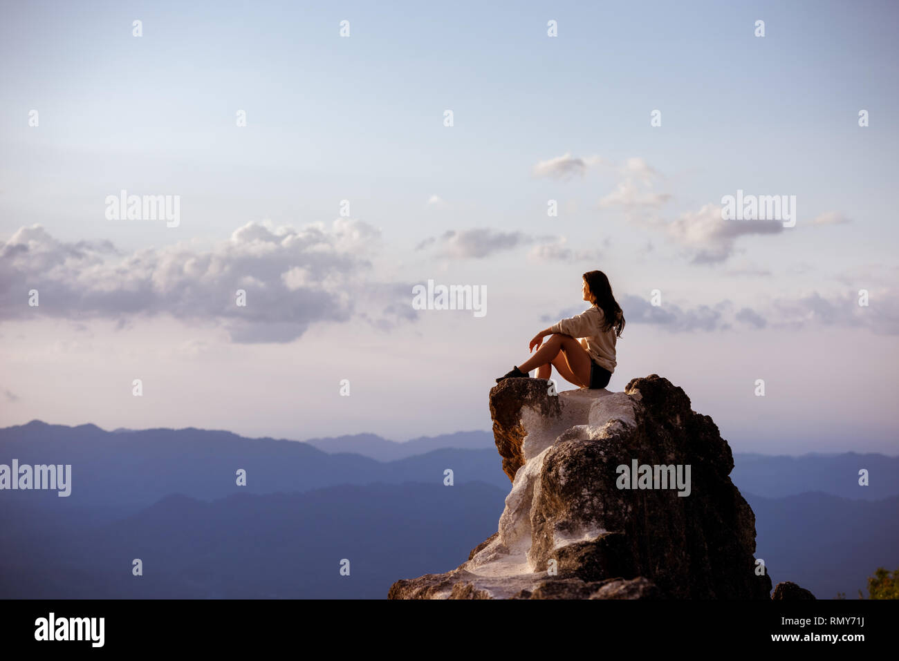 Beautiful girl sits on big rock at sunset time and relax. Space for text Stock Photo