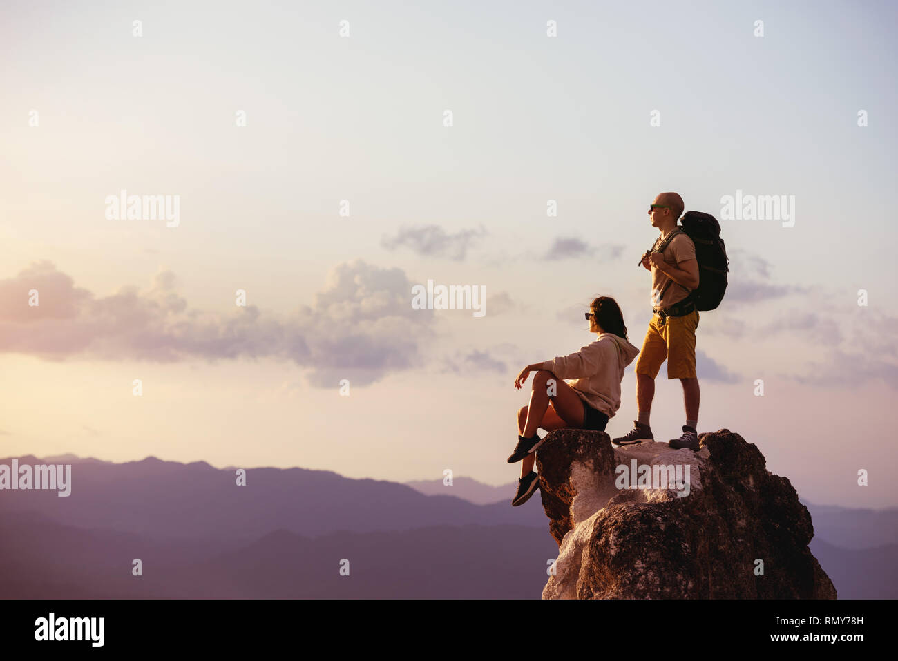 Couple of backpackers relaxing on big rock at sunset time. Space for text Stock Photo