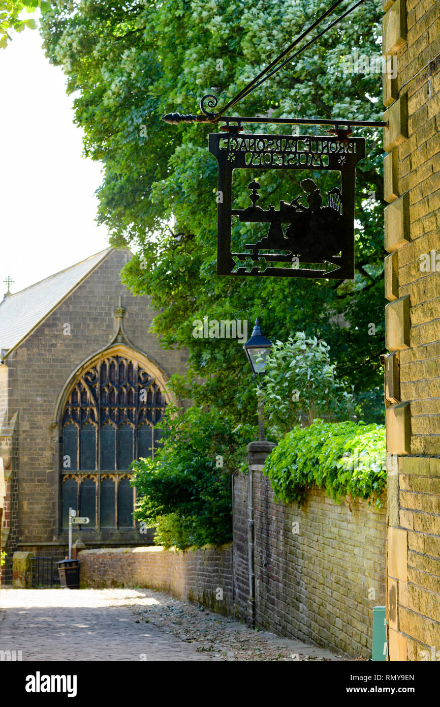 Close-up of black metalwork sign hanging on exterior wall of Bronte Parsonage Museum (Brontes home) & church beyond - Haworth, Yorkshire, England, UK. - Stock Image