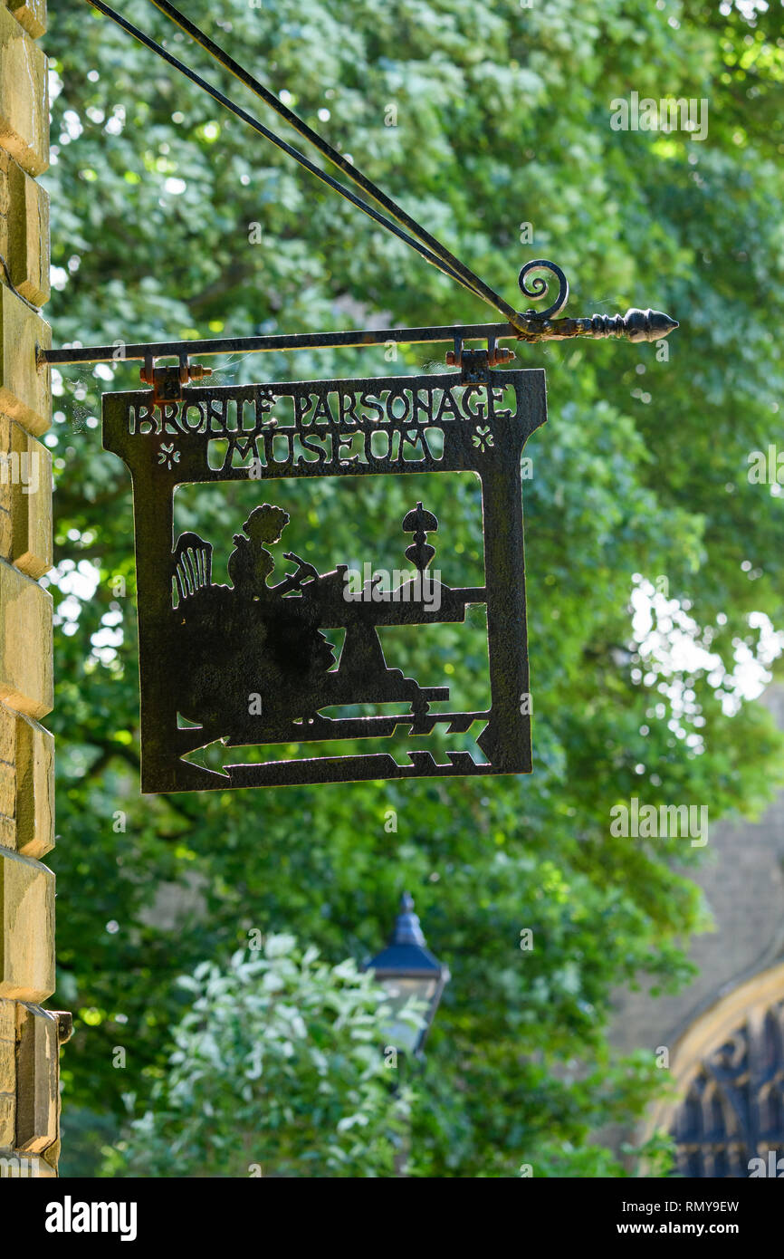 Close-up of black metalwork sign (cut out design) hanging high on exterior wall of Bronte Parsonage Museum - Haworth, West Yorkshire, England, UK. - Stock Image