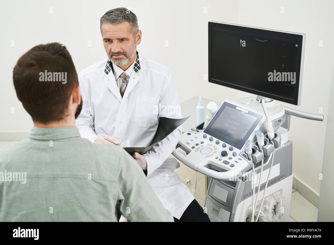 Patient sitting in medical cabinet with professional doctor and consulting. Serious therapist wearing in medical white gown talking, holding holder. Modern equipment for ultrasound examination. - Stock Image