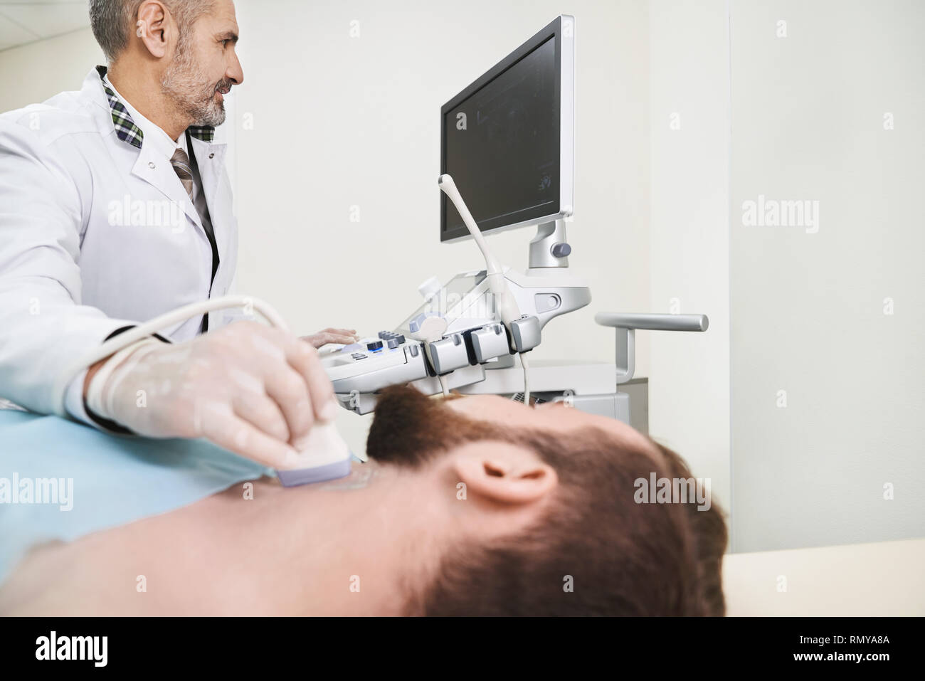 Sonography, ultrasound diagnostics of lymph nodes on neck. Bearded man lying in medical cabinet. Doctor wearing in white, medical gown and gloves doing examination with ultrasound probe. - Stock Image