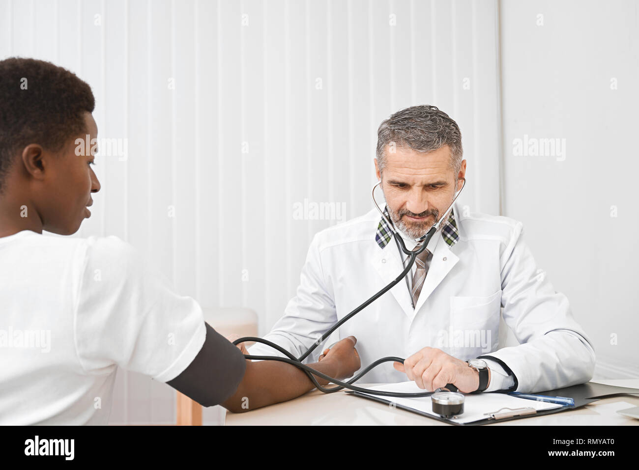 Young african man sitting, holding hand on table, while doctor measuring blood pressure. Professional therapist using sphygmomanometer for examination. Concept of cardiology. - Stock Image