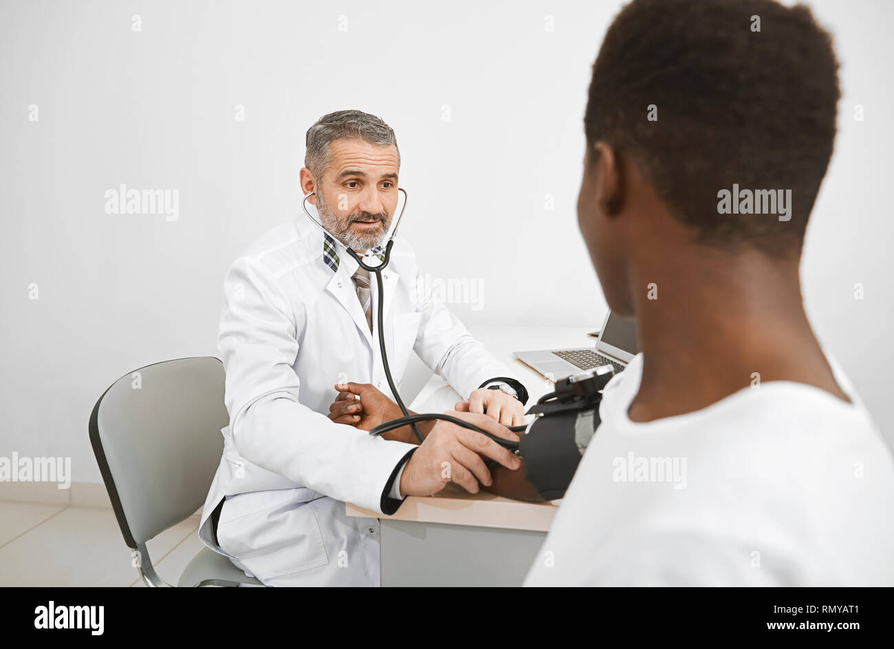 Doctor using sphygmomanometer for measuring blood pressure of patient. African man sitting on consultation, holding hand on table. Doctor wearing in medical white gown. - Stock Image