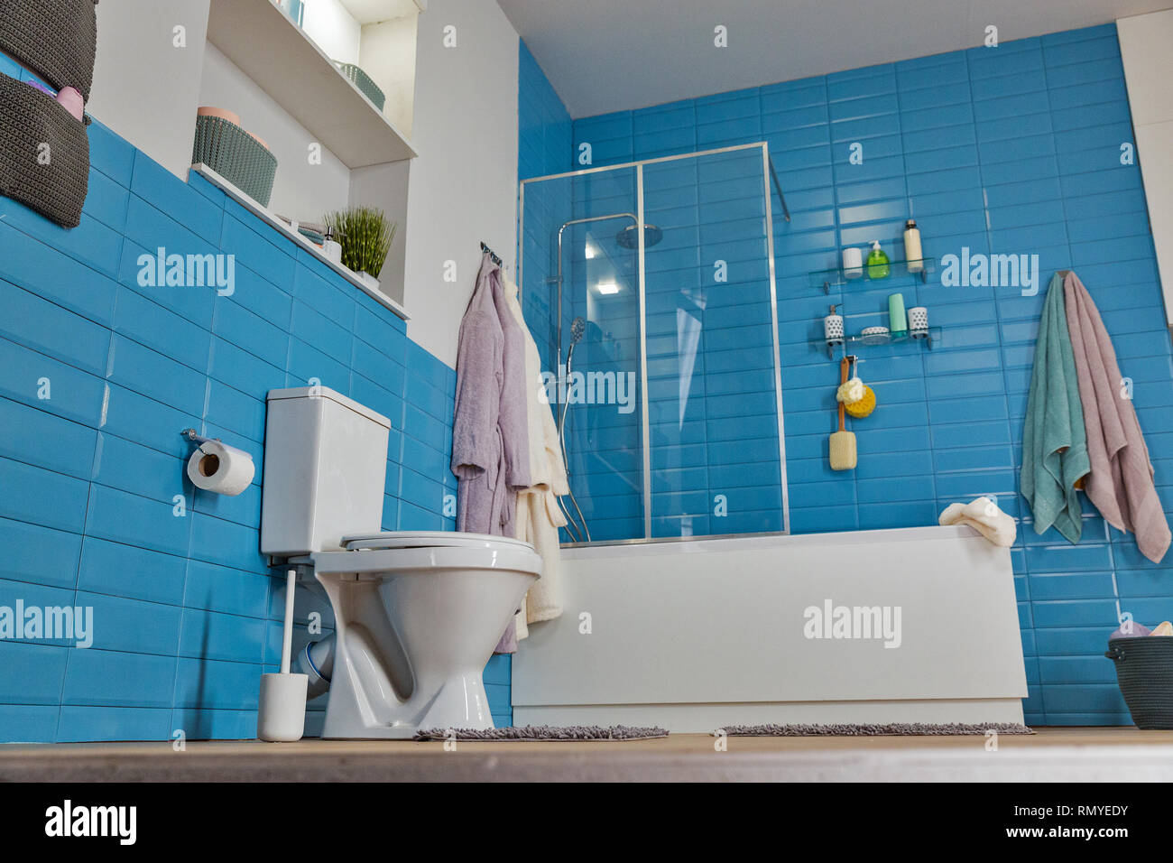 Modern Bathroom With White Toilet Bowl And Blue Tile Floor View Stock Photo Alamy