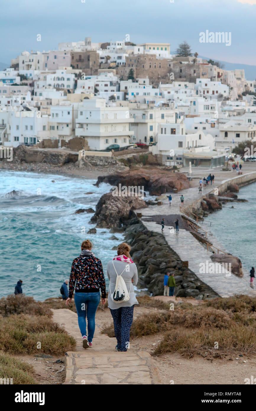 Women walking towards Naxos City on a stormy day near the Portara of Naxos, Cyclades, Greece - Stock Image
