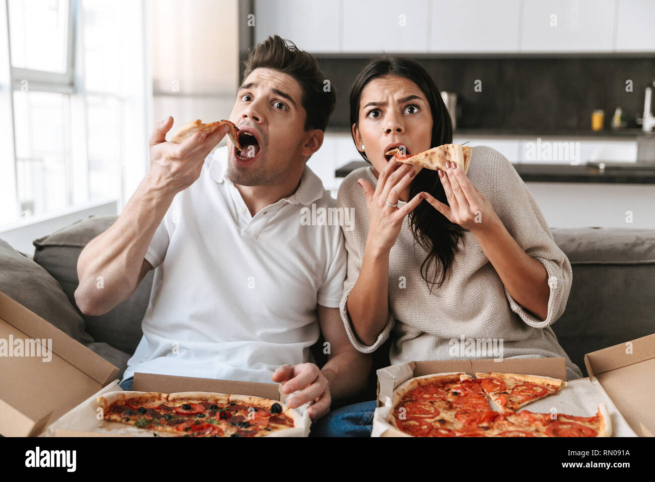 Cheerful young couple sitting on a couch at home, eating pizza, watching TV - Stock Image