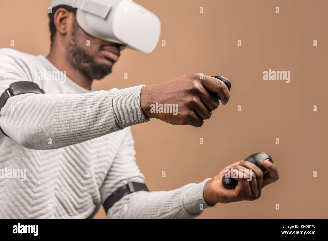 Man in VR glasses now is playing 3D game but Mankind stands on the threshold of a new era of controlling objects in virtual reality from the real worl - Stock Image