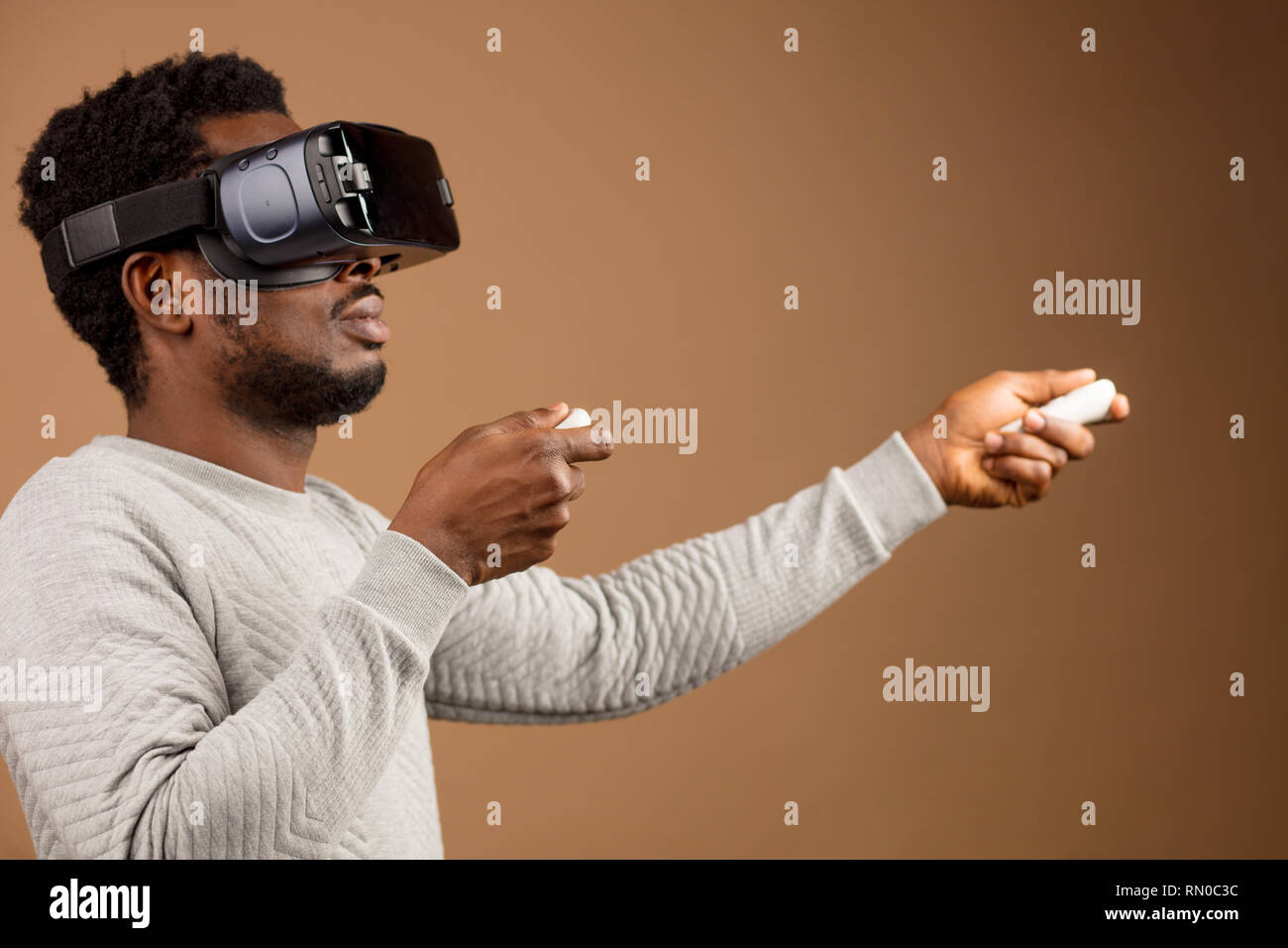 Dark-skinned millennial tourist in casual clothing wearing glasses with head-mounted display for smart phone, operating with controllers in hands, doi - Stock Image
