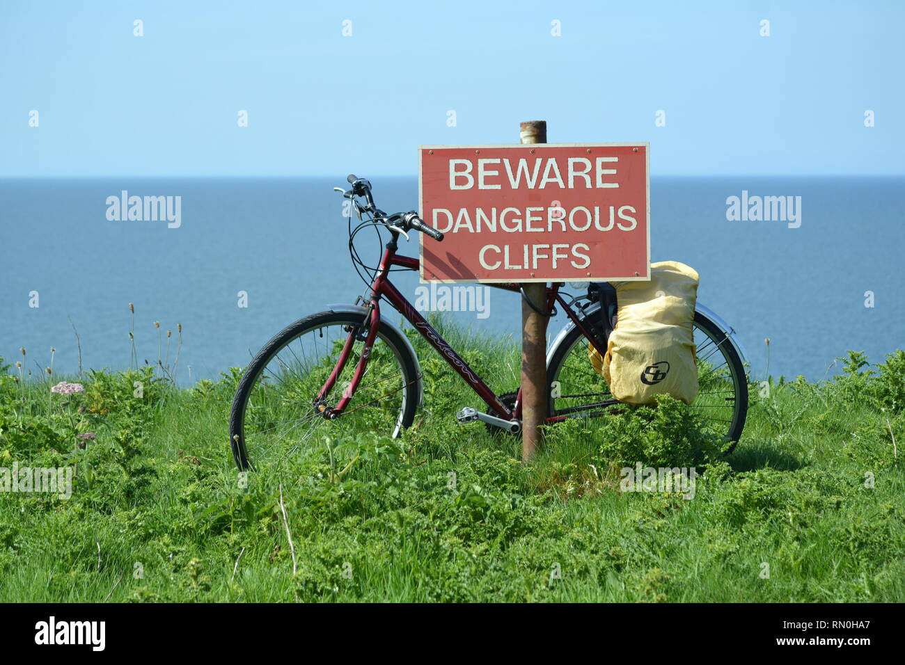Dangerous cliffs warning sign with a bike leant against it. Filey North Yorkshire. - Stock Image