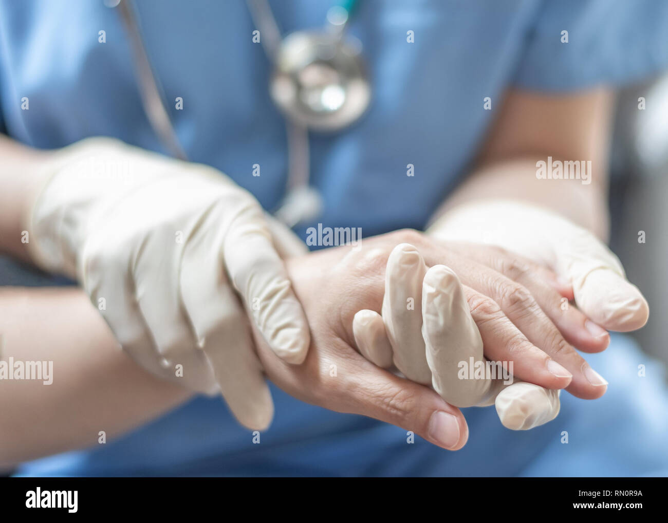 Surgeon, surgical doctor, anesthetist or anesthesiologist holding patient's hand for health care trust and support in professional surgical operation - Stock Image