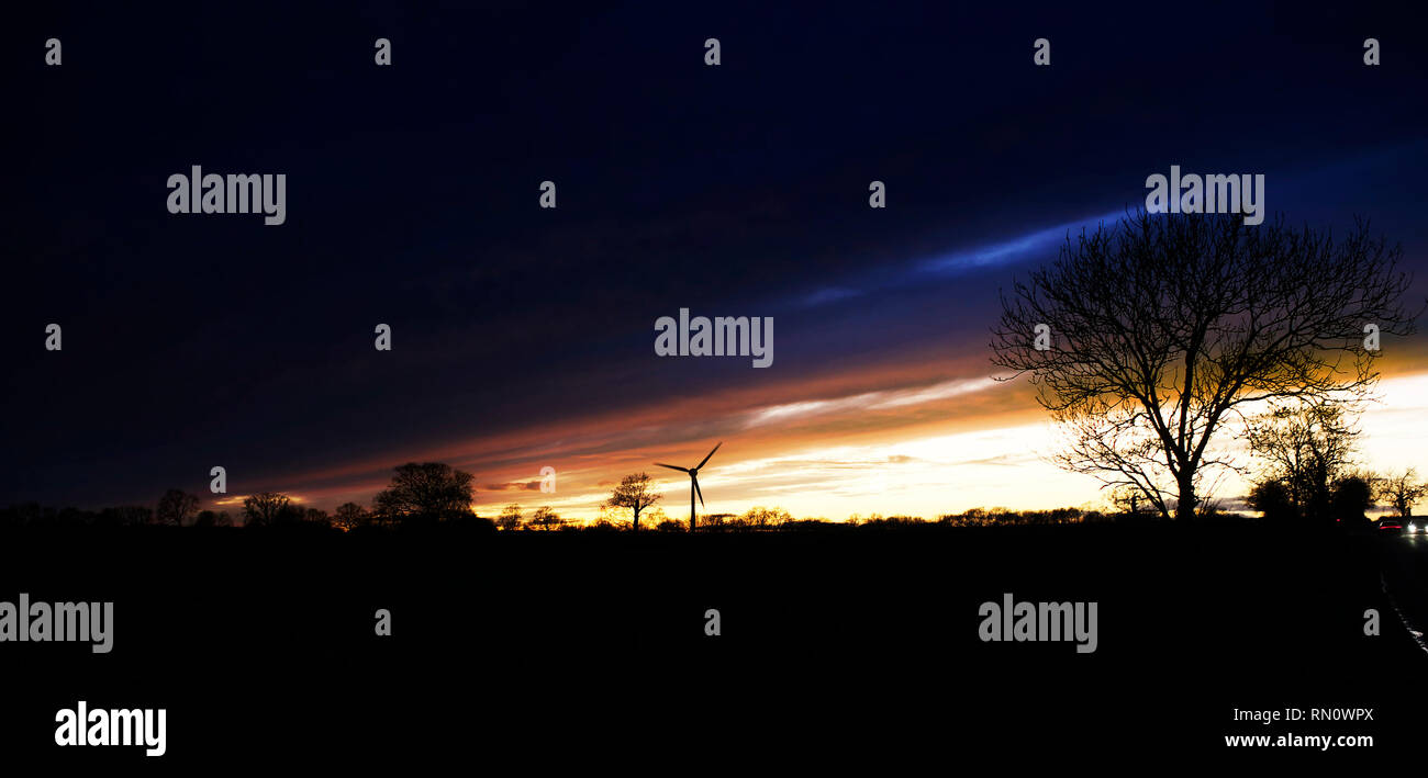 a single wind turbine in the distance over fields in a typical english country scene at sunset - Stock Image