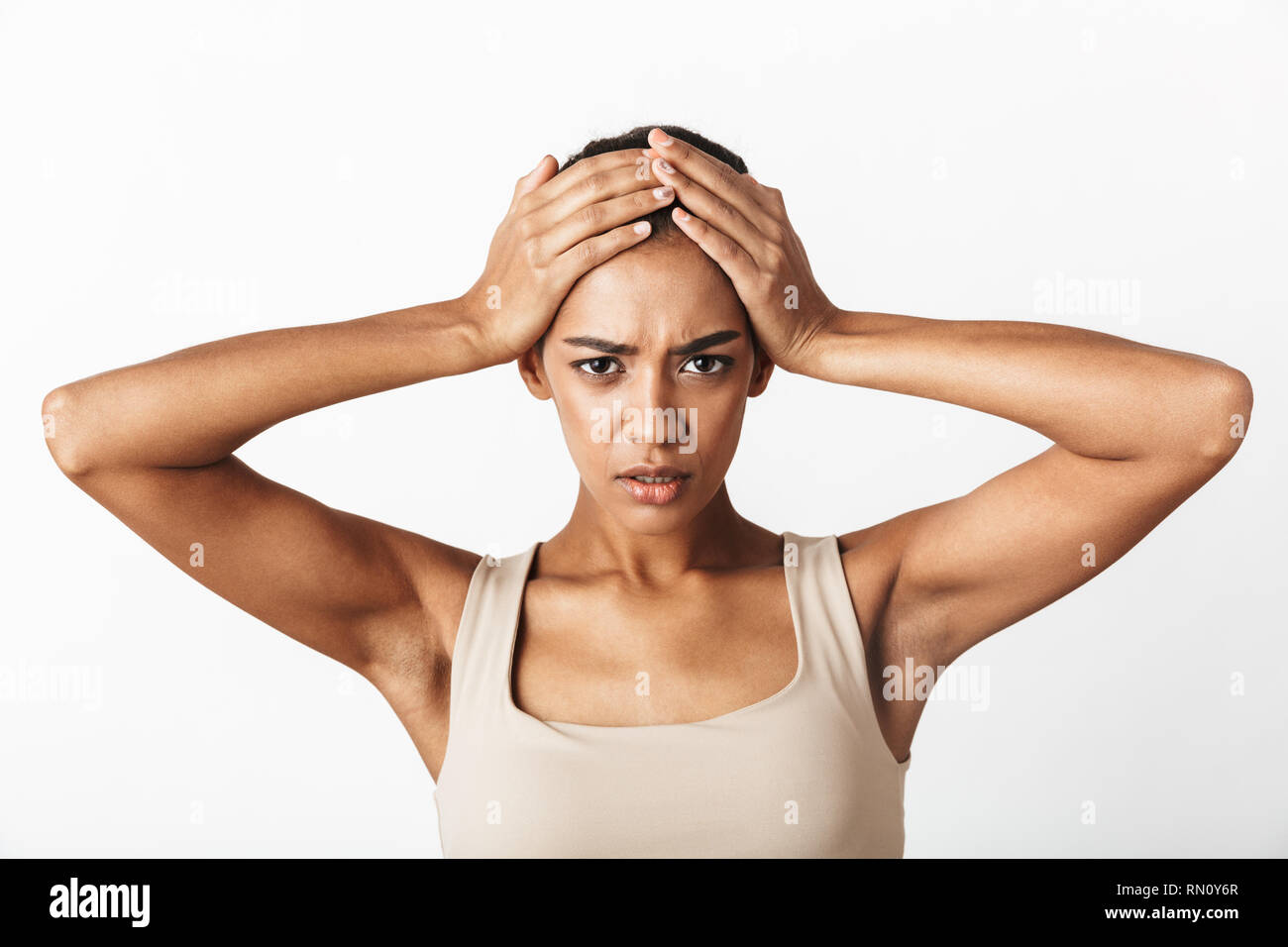 Beautiful young sad african woman casually dressed standing isolated over white background, having a headache - Stock Image