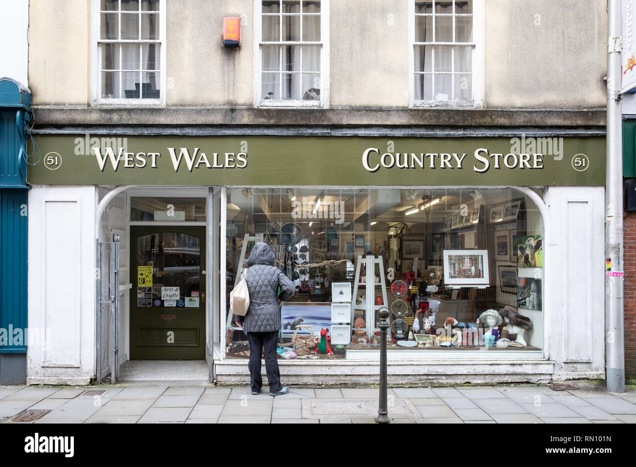 A lady looks through the window at the West Wales Country Store shop in Kings Street Carmarthen. They sell countryside outdoor pursuits. - Stock Image