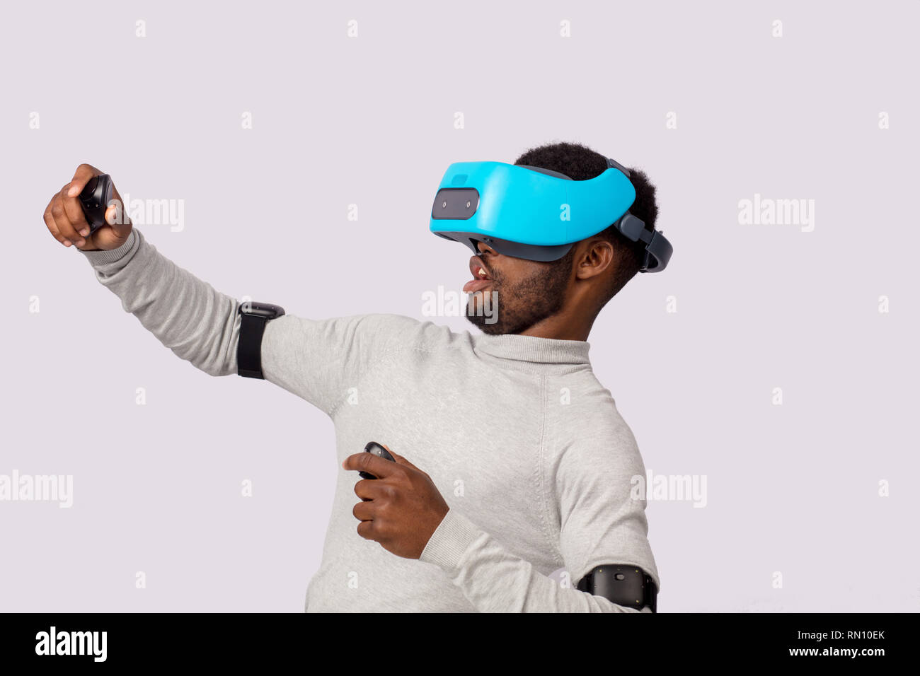 6e71a6a1ed9 Amazed excited African businessman in white sweater using mobile vr headset