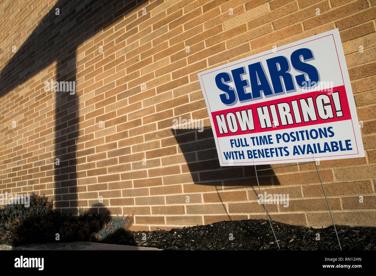 A 'Now Hiring' sign outside of a Sears retail store location in Harrisburg, Pennsylvania on February 9, 2019. - Stock Image