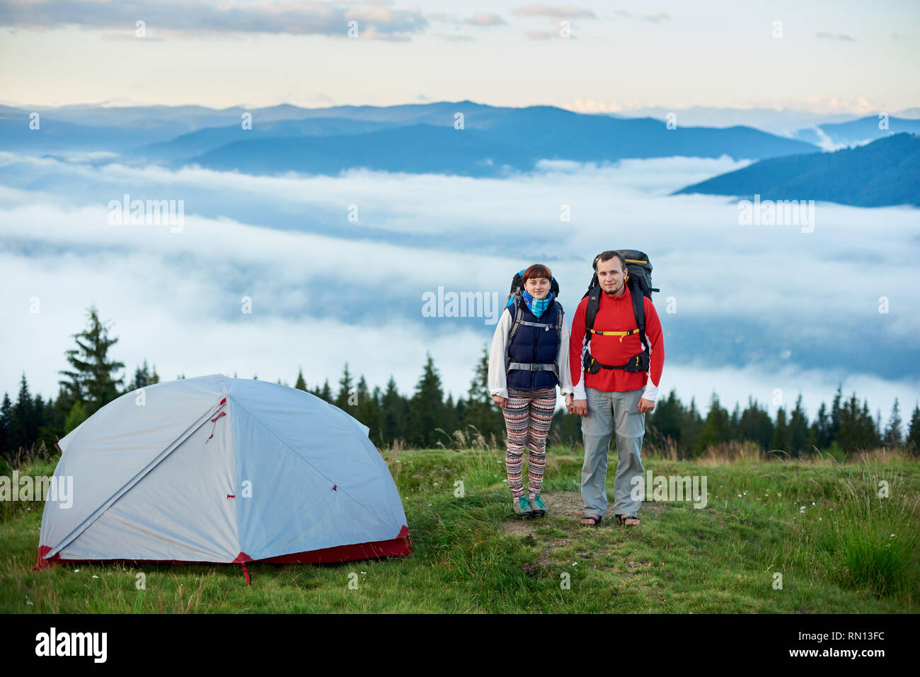 Pair of tourists with backpacks near the tent on the blurred background of the mighty mountains on which lies the fog. Concept of a healthy lifestyle - Stock Image