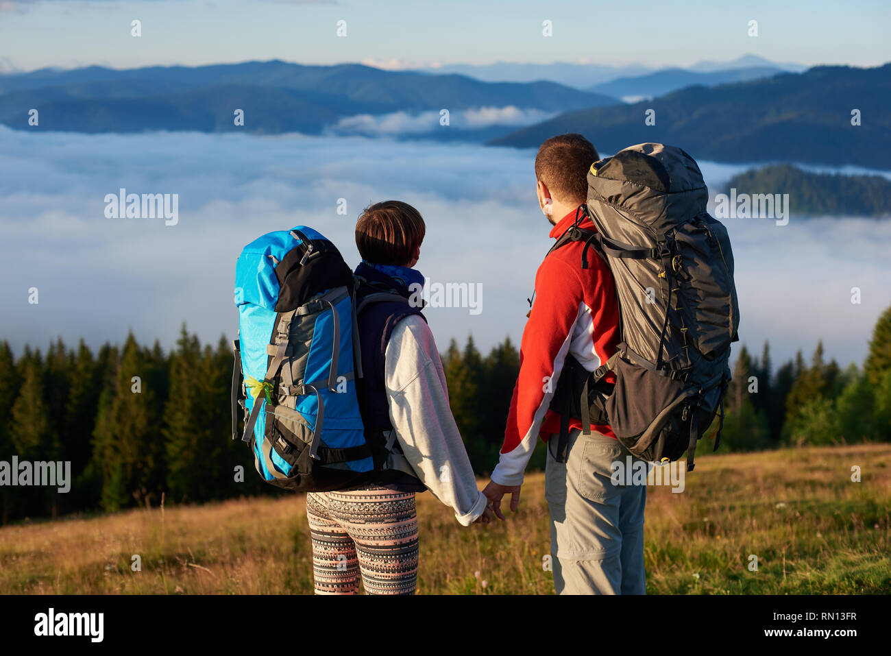 Rear view two people holding hands enjoy the scenery of a dense haze over mighty mountains in the rays of a sunset. Close-up - Stock Image