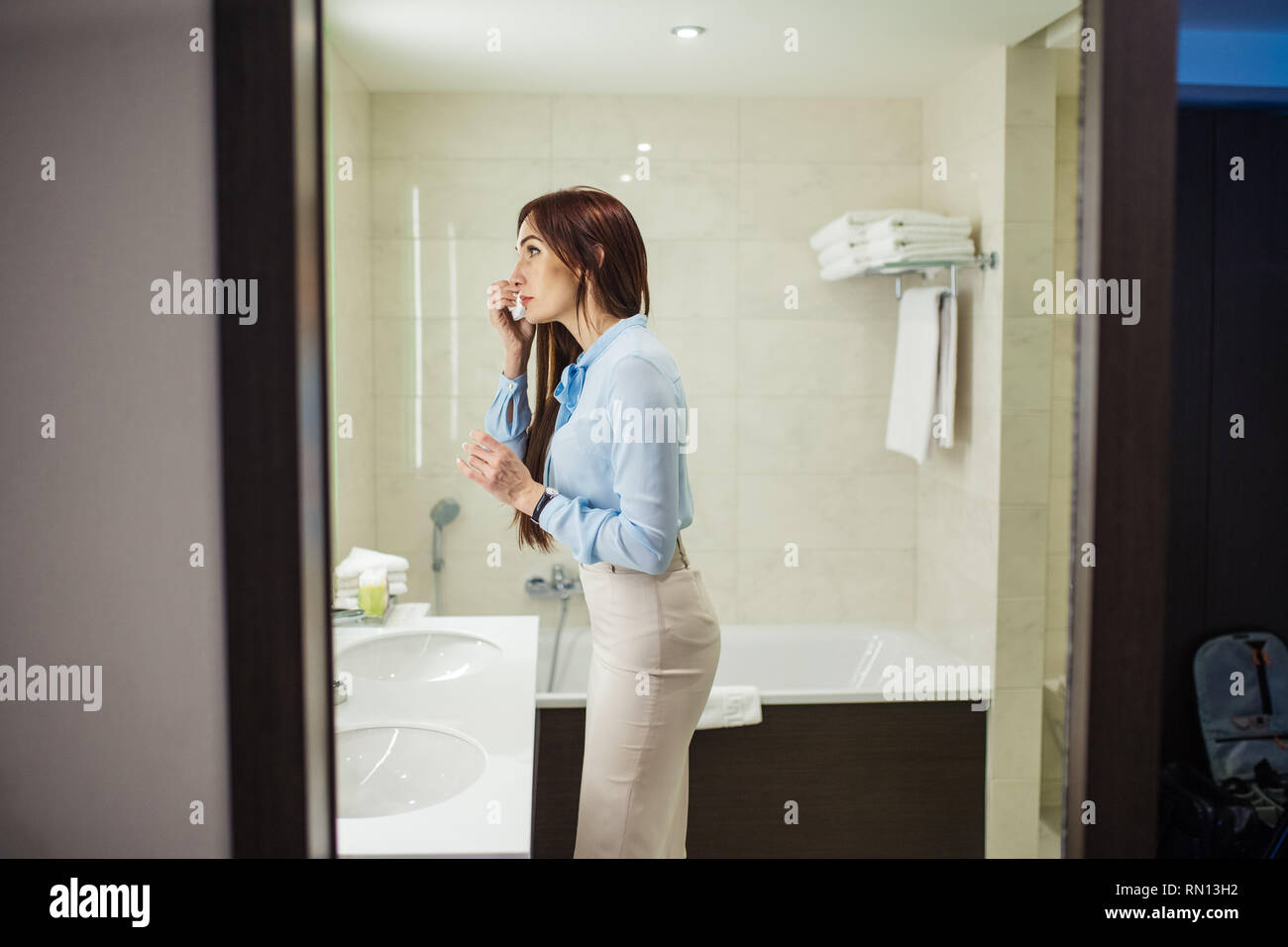 Image of pretty female dressed in romantic blue blouse, pencil skirt looking at the mirror while washing her hands in the morning over white sink in b - Stock Image
