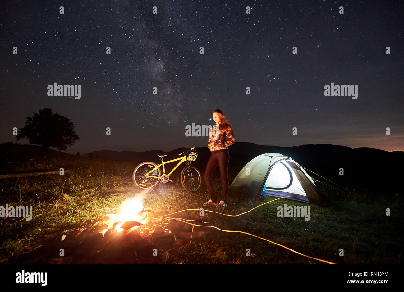 Young woman cyclist resting at night camping near burning campfire, illuminated tourist tent, mountain bike under evening sky full of stars and Milky way. Outdoor activity and tourism concept - Stock Image