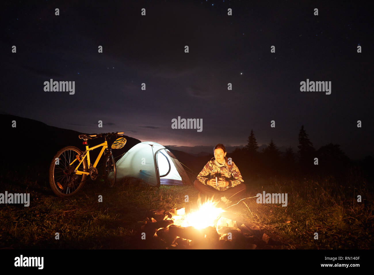 Young woman cyclist enjoying at night camping near burning campfire, illuminated tourist tent, mountain bike under beautiful evening sky full of stars. Outdoor activity and tourism concept - Stock Image