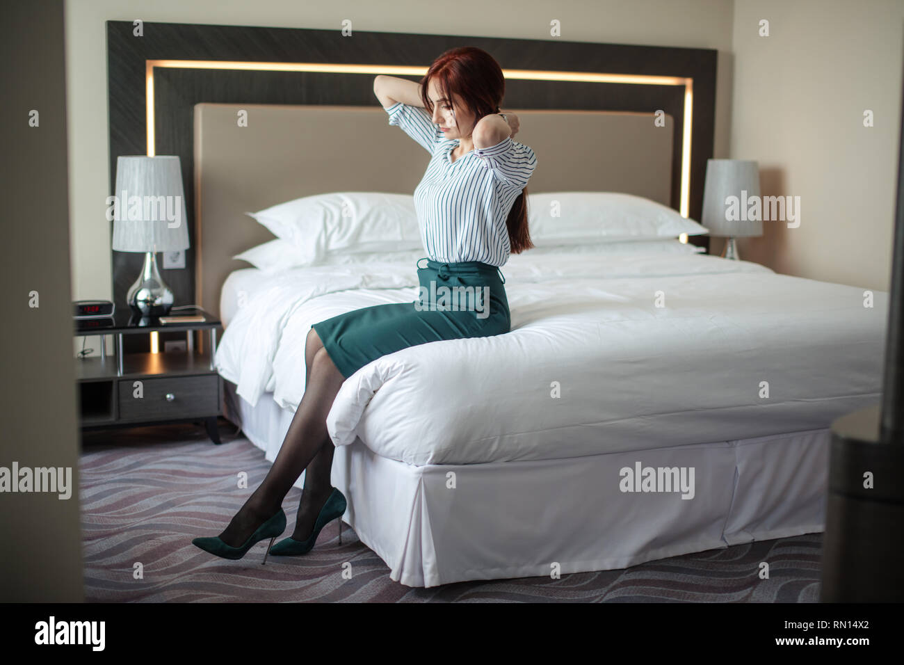 Elegantly dressed business woman in green pencil skirt and stilettos, relaxing on hotel room bed after a long business trip. - Stock Image