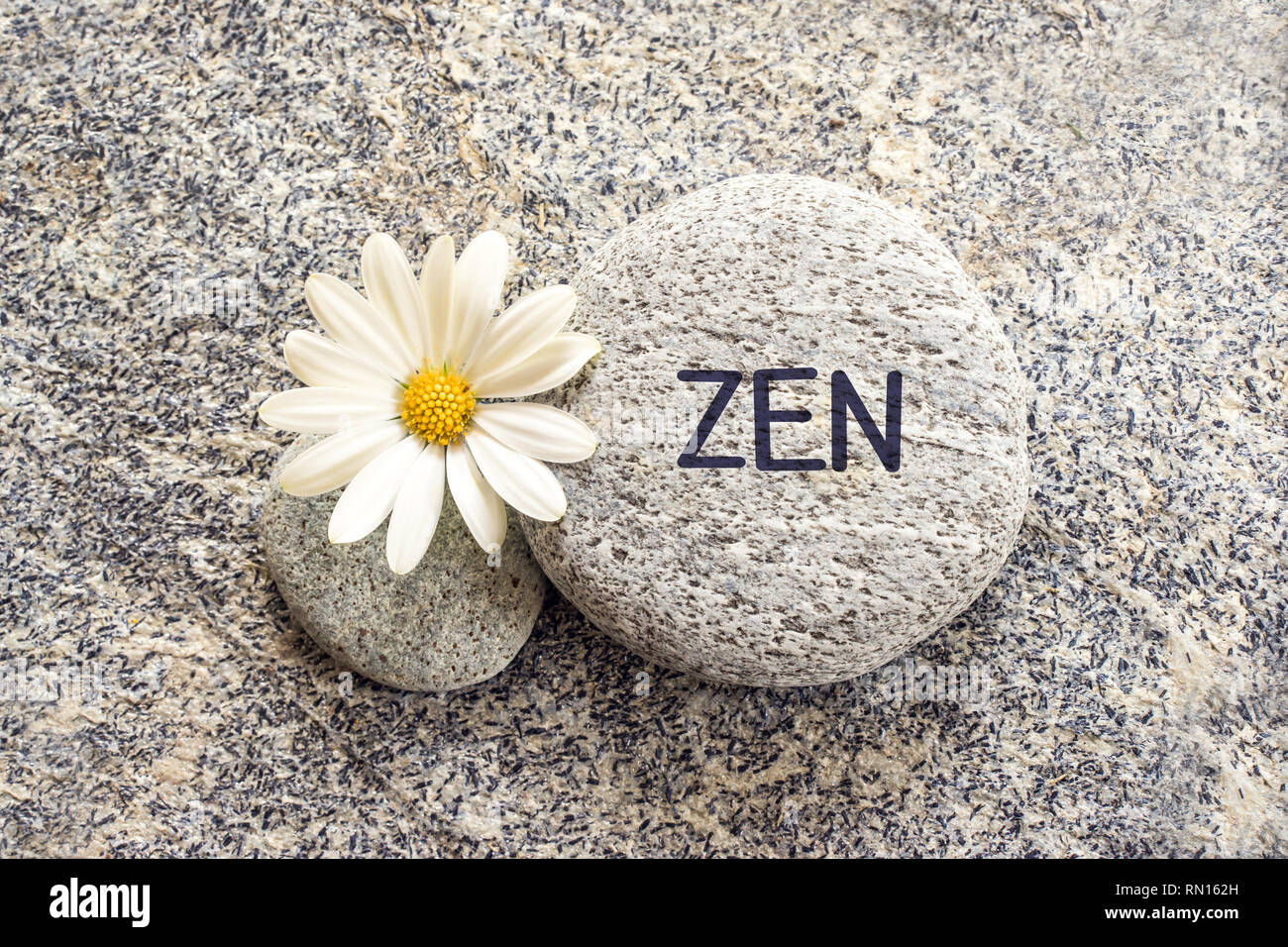 Word zen written on a stone background with a daisy - Stock Image