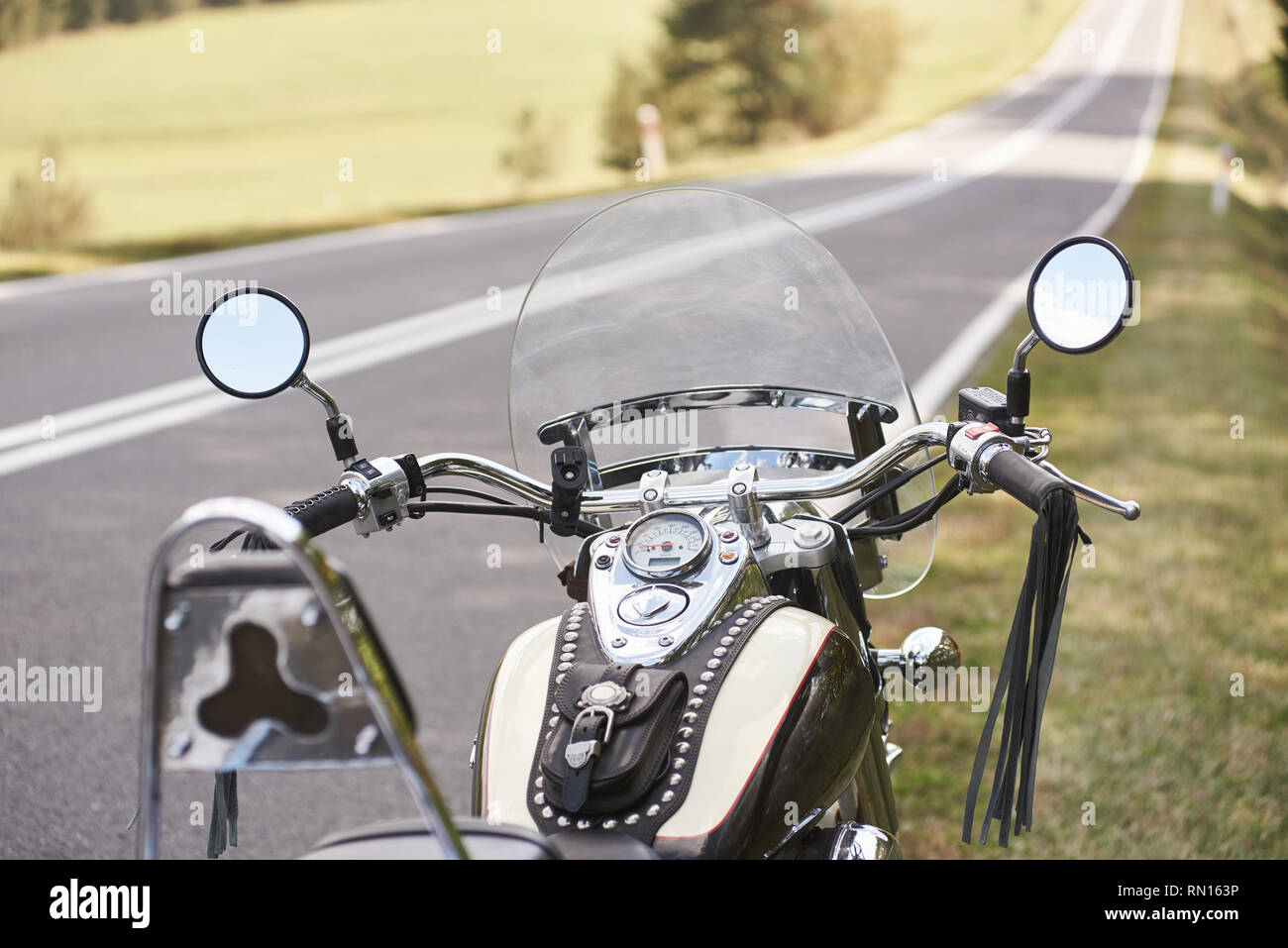 Detail of black shiny powerful motorcycle parked on roadside on blurred sunny outdoors background. Modern transportation technology, speed and long-distance traveling concept. - Stock Image