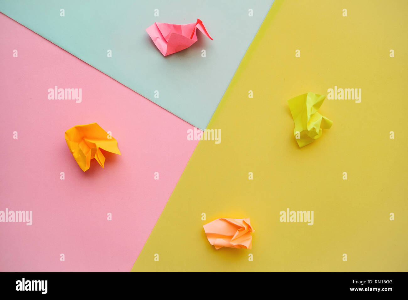 Crumpled sheets of colored paper on a multi-colored background. Lack of ideas and frustration. - Stock Image
