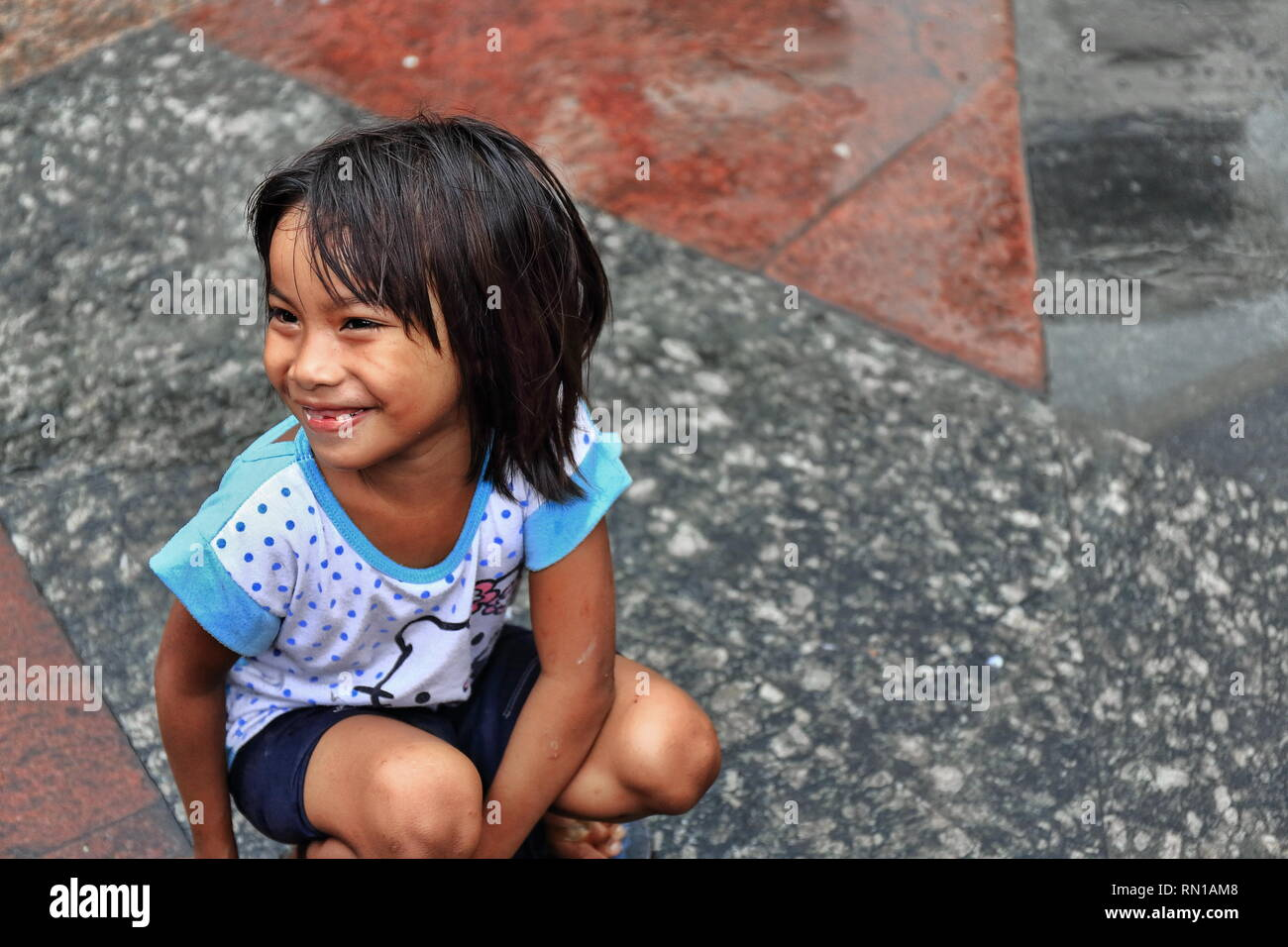 Manila, Philippines-October 24, 2016: Little local girl plays at the yard off the Quiapo Church-Minor Basilica of the Black Nazarene's W.wall while wa - Stock Image