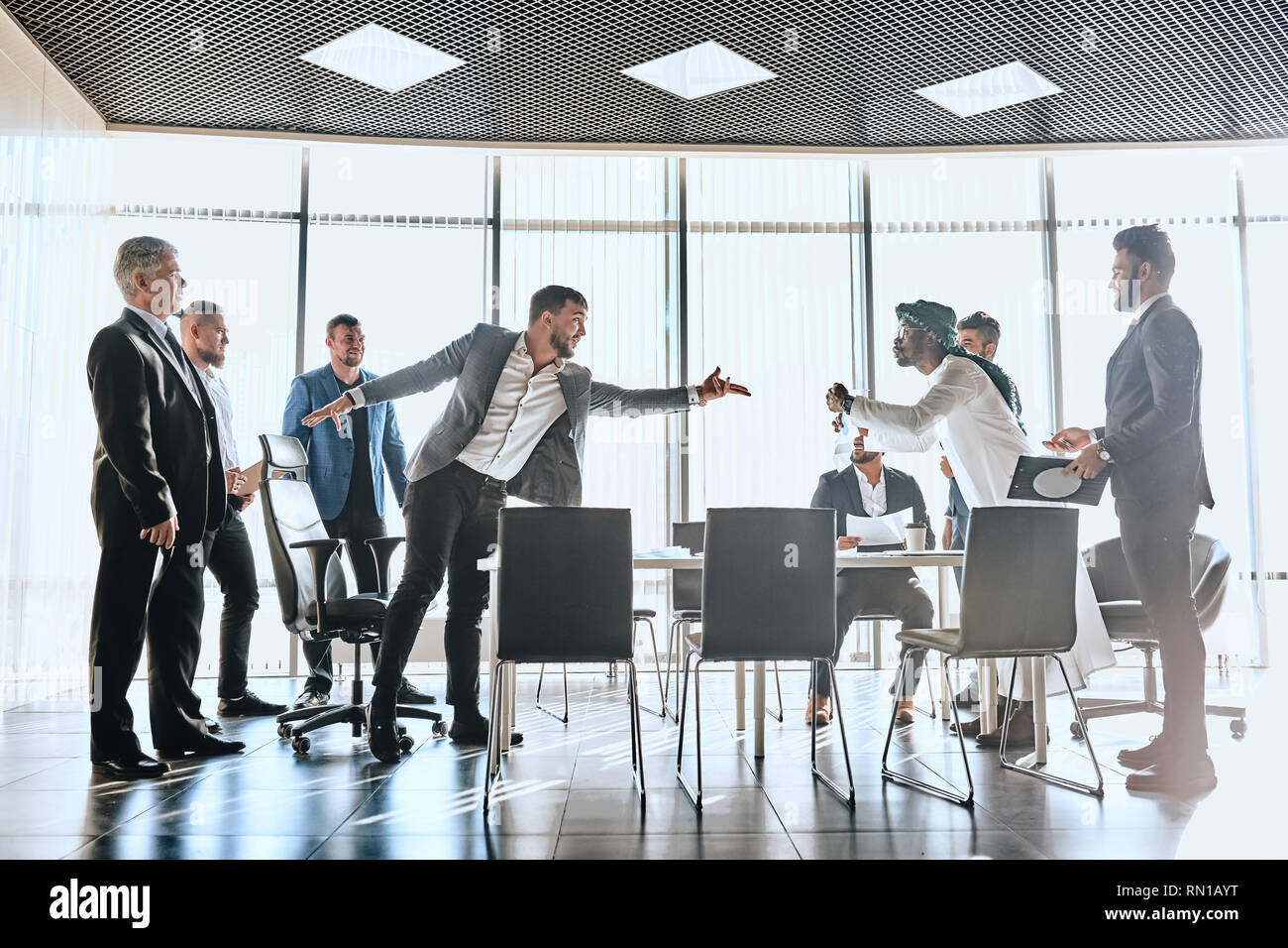 Angry Caucasian businessman threatens Arab colleague, , bullying and discrimination. fauil and failure concepts - Stock Image