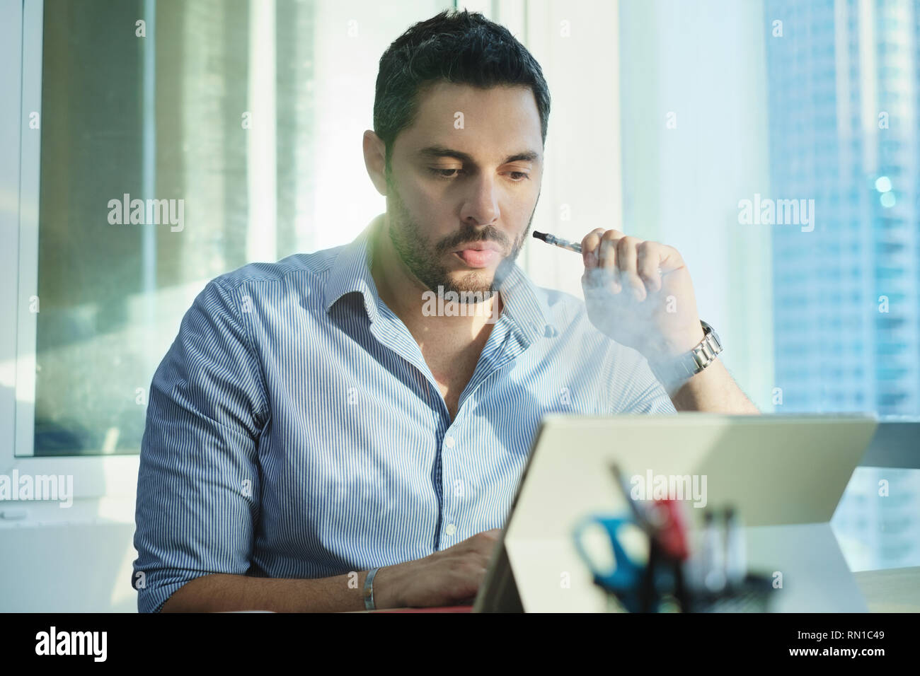 Ex-smoker Man Smoking Electronic Cigarette In Office While Working - Stock Image