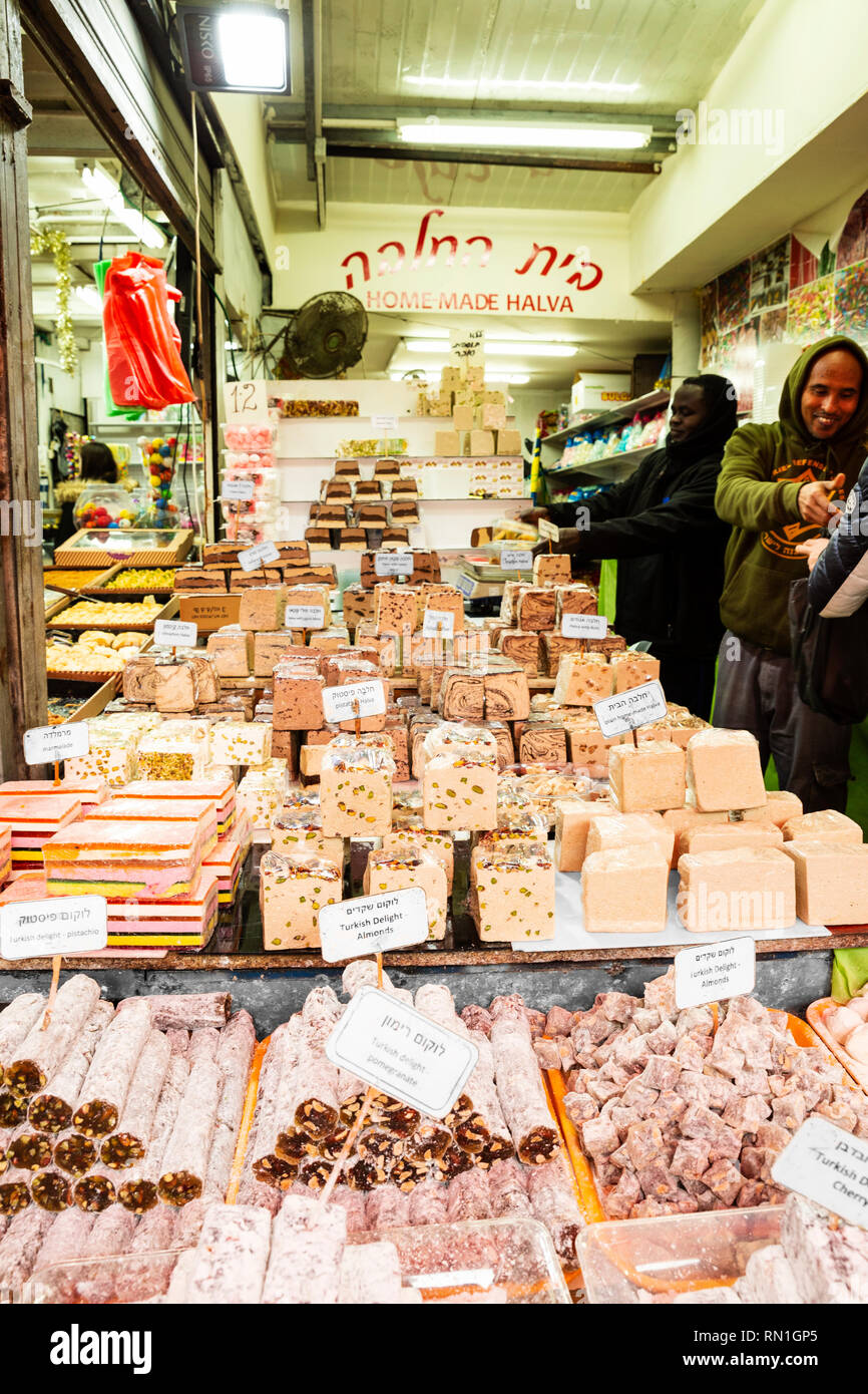 Tel Aviv, Yafo, Carmel Market, Israel - December 28, 2018: A happy smiling sellers selling home made halva (oriental sweet) at the famous Carmel Marke - Stock Image