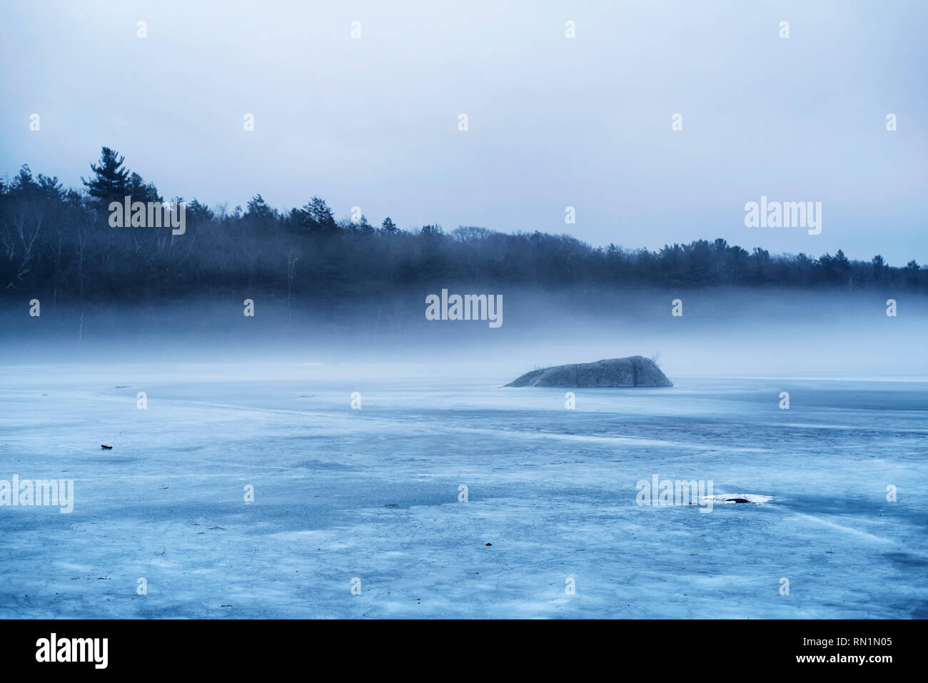 Mists rising above the frozen waters of Burr Pond State Park in winter in new england. - Stock Image