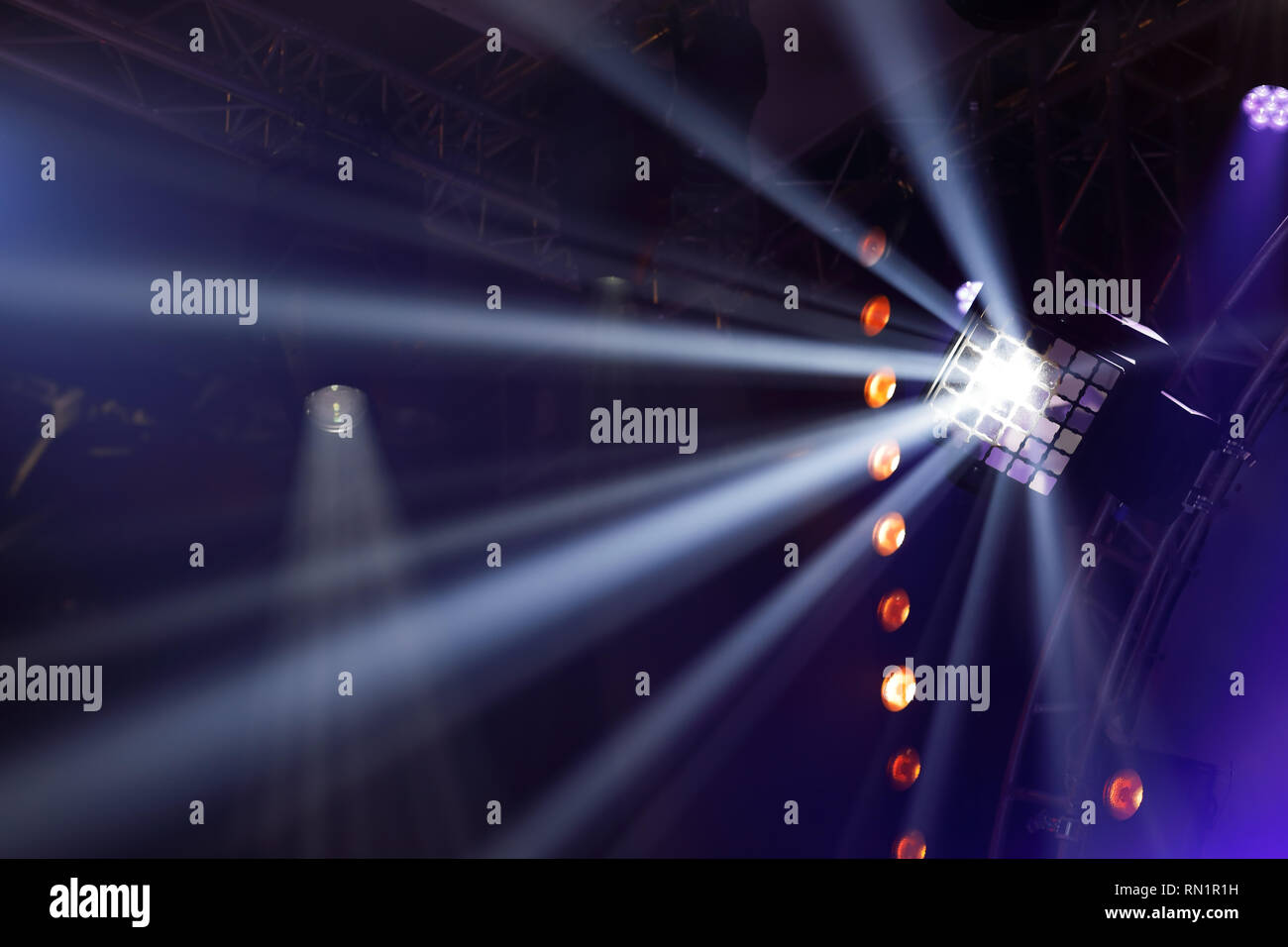 Various types of stage lighting fixtures hanging on the farm. White beams of stage light. - Stock Image