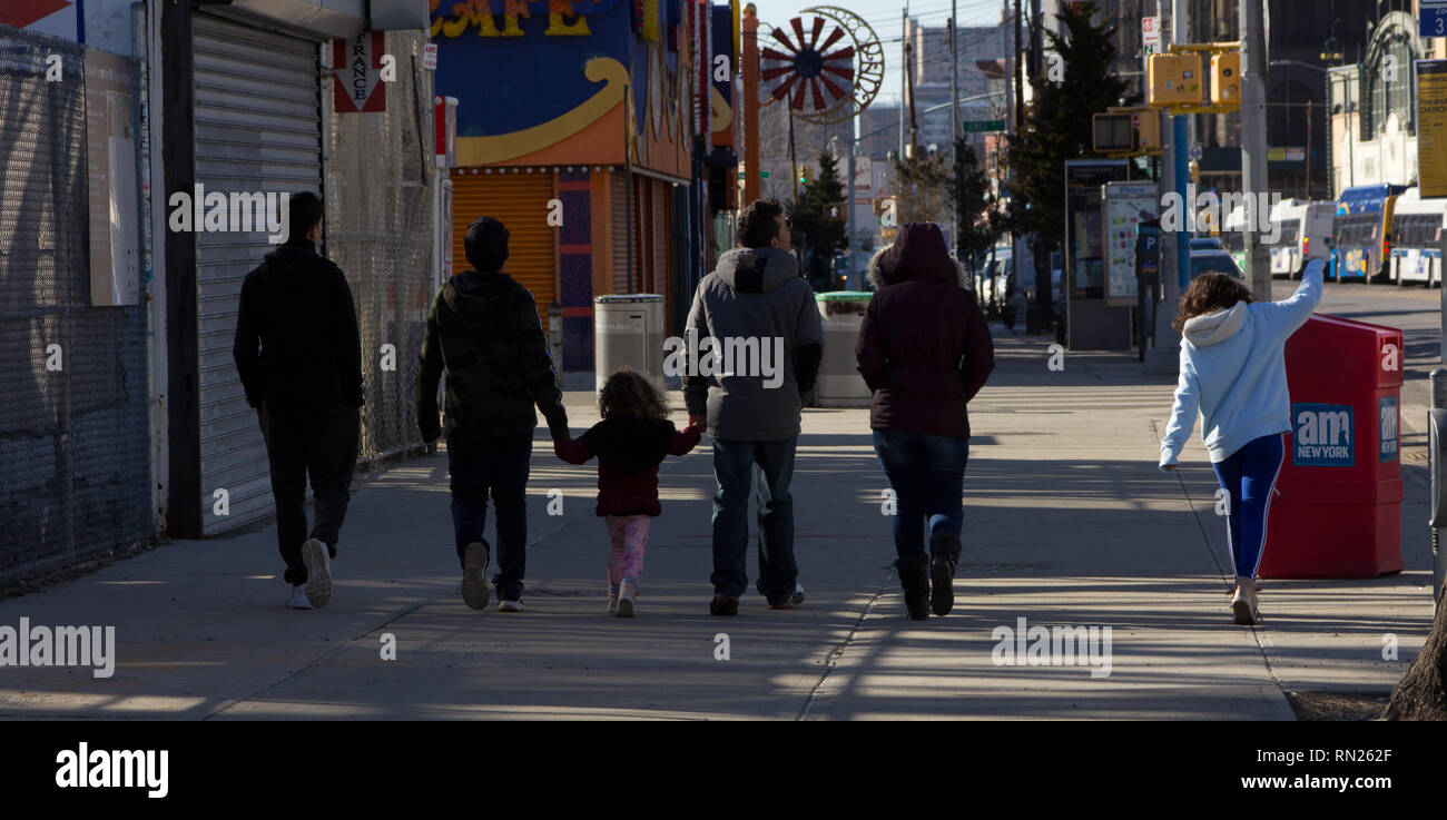 New York, USA. 16th February, 2019. A group of people walk side-by-side on Surf Avenue at Coney Island in Brooklyn, enjoying the day, a sunny winter Saturday afternoon in February, as the shadows of Luna Park's wooden Cyclone roller coaster (out of view on the left), listed on the New York State Register of Historic Places, fall upon them. Two of the people stroll on either side of a little girl with curly hair, each holding one of her hands. Another girl balances as she walks along the cracks in the sidewalk (pavement), an AM New York newspaper rack in front of her. Kay Howell/Alamy Live News - Stock Image