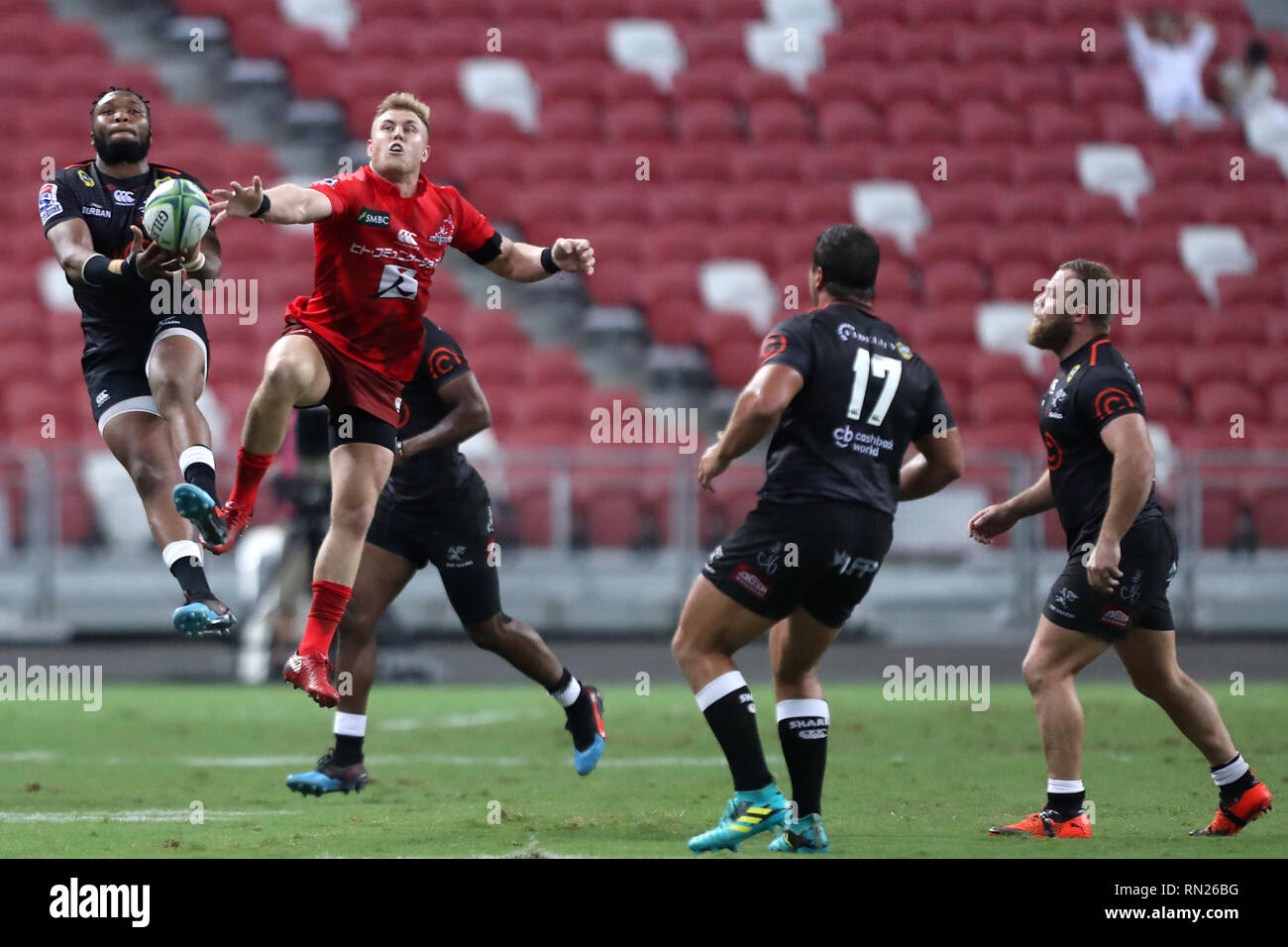 Singapore. 16th Feb, 2019. Lukhanyo Am, left, of the Sharks competes for the ball with Shane Gates of the Sunwolves during the round 1 Super Rugby match between the Sunwolves and the Sharks at the National Stadium. Credit: Paul Miller/ZUMA Wire/Alamy Live News - Stock Image