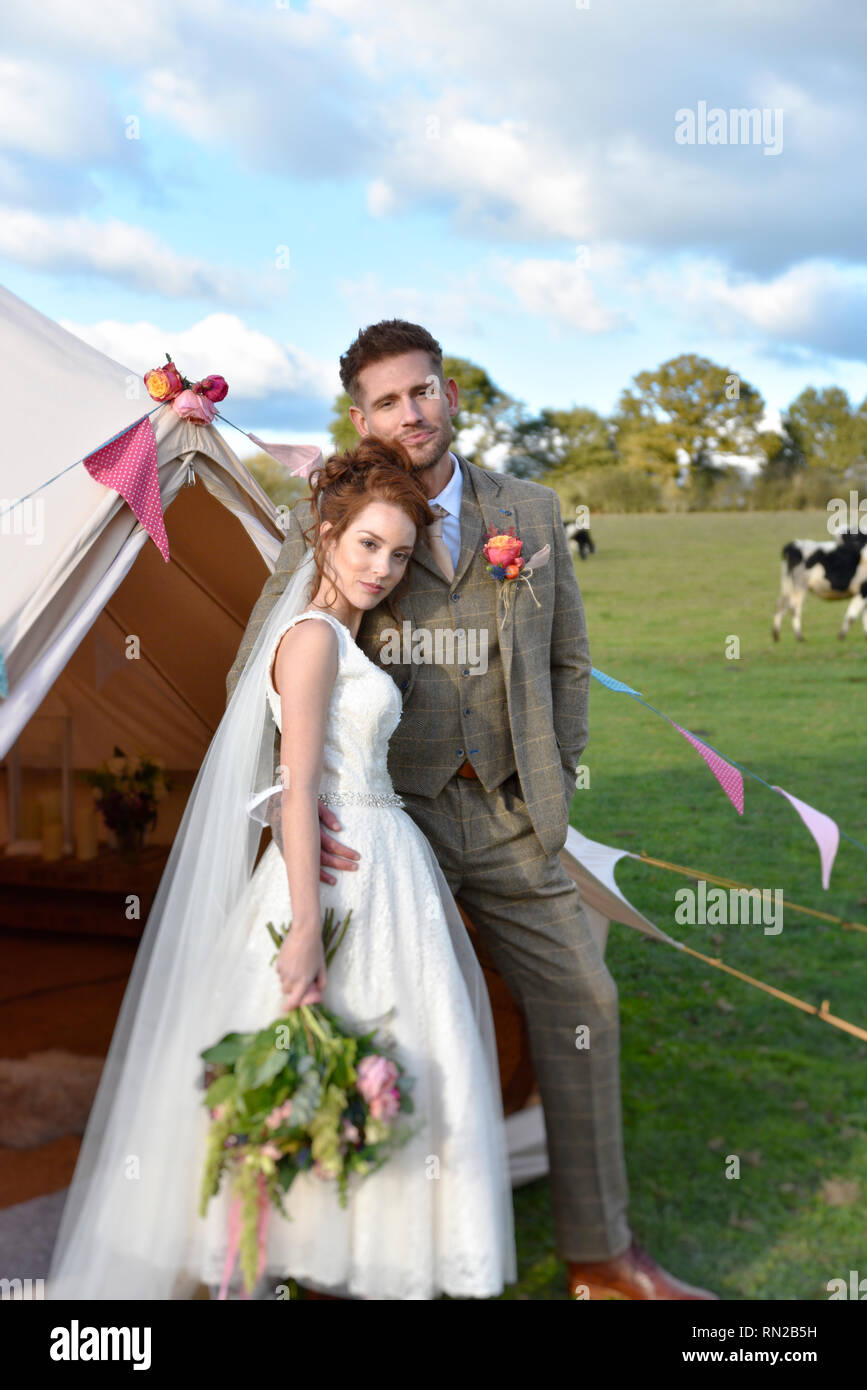 A Beautiful Couple Get Married In A Romantic Farm Location She Is A Redhead And Wers A Short Vintage Wedding Dress He Is Tall And Has Tatoos Stock Photo Alamy