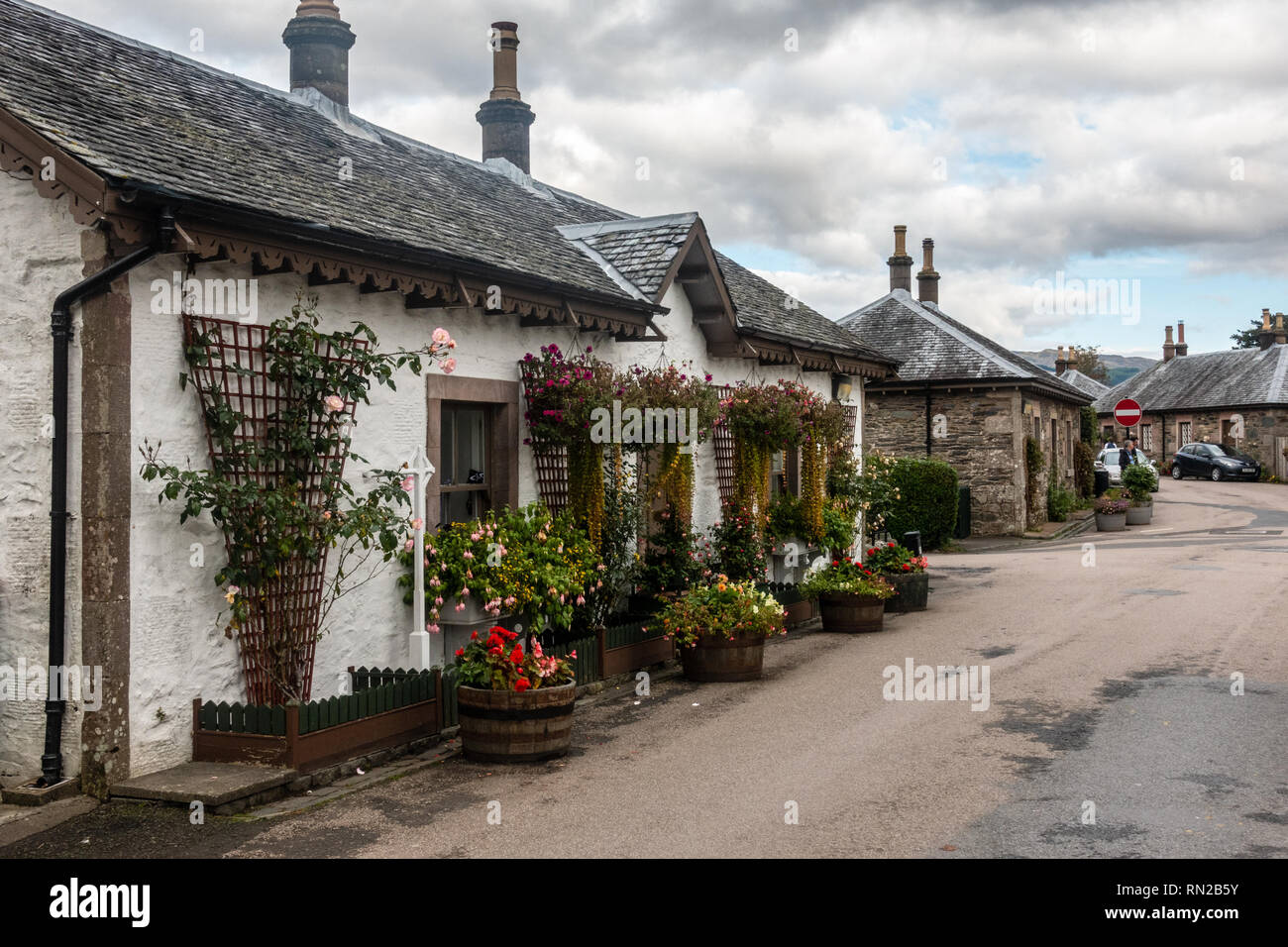 Luss, Scotland, UK - September 28, 2017: Climbing flowers and hanging baskets decorate quaint traditional cottages in the village of Luss in Scotland' - Stock Image