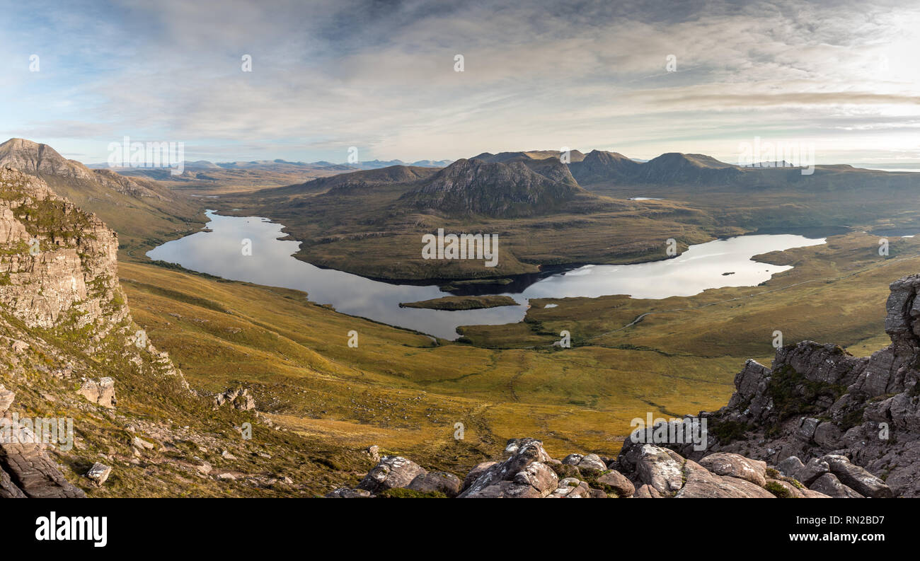 Beinn an Eoin and Ben More mountains rise behind Loch Lurgainn lake as viewed from Stac Pollaidh in the northwest Highlands of Scotlands. - Stock Image