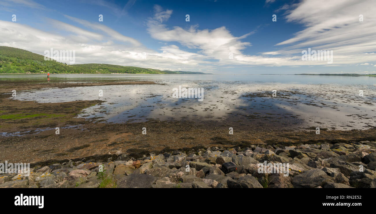 Blue sky is reflected in the waters of the Moray Firth at Inverness in the Highlands of Scotland. Stock Photo