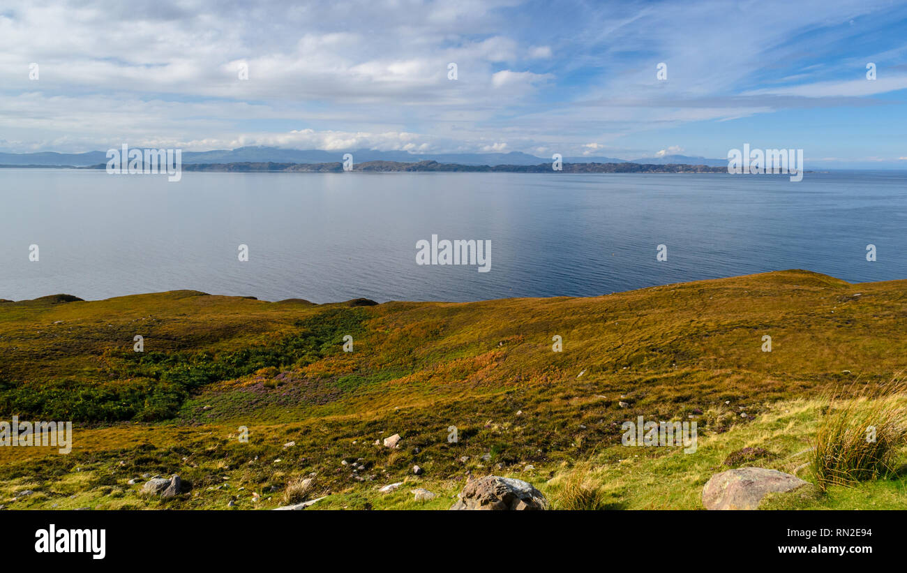 Sun shines on the Hebridean islands of Rona and Skye, across a blue sea from the Applecross Peninsula in the Highlands of Scotland. Stock Photo