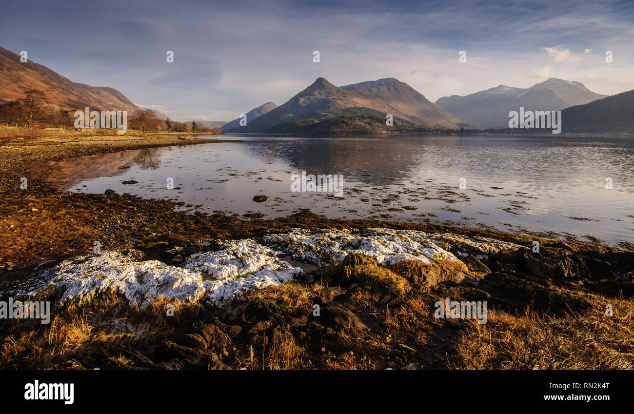 The distinctive shaped Pap of Glencoe mountain is reflected in the calm water of Loch Leven, a fjord-like inlet of the Atlantic Ocean, on a clear wint - Stock Image