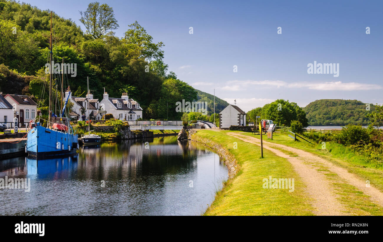 Crinan, Scotland, UK - June 3, 2011: A small yacht and fishing boat are moored beside traditional cottages on the Crinan Canal in the West Highlands o Stock Photo