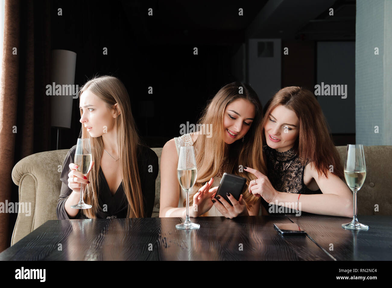 always connected, internet addiction, young girls in cafe Stock Photo